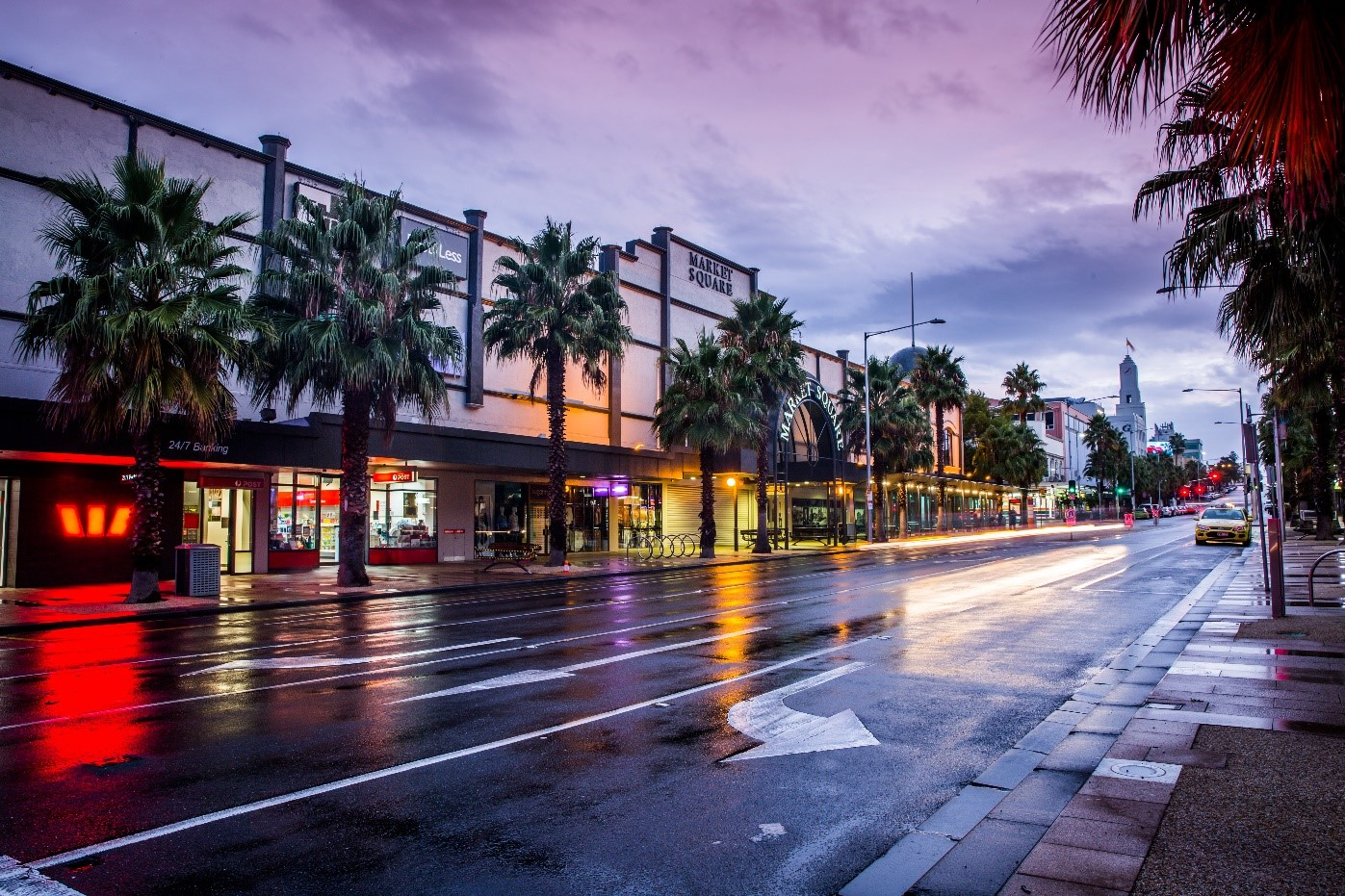 A view down Moorabool Street, central Geelong in the early evening. The road is wet and the light from Westpac and the Market Square shops is reflecting on the tarmac.